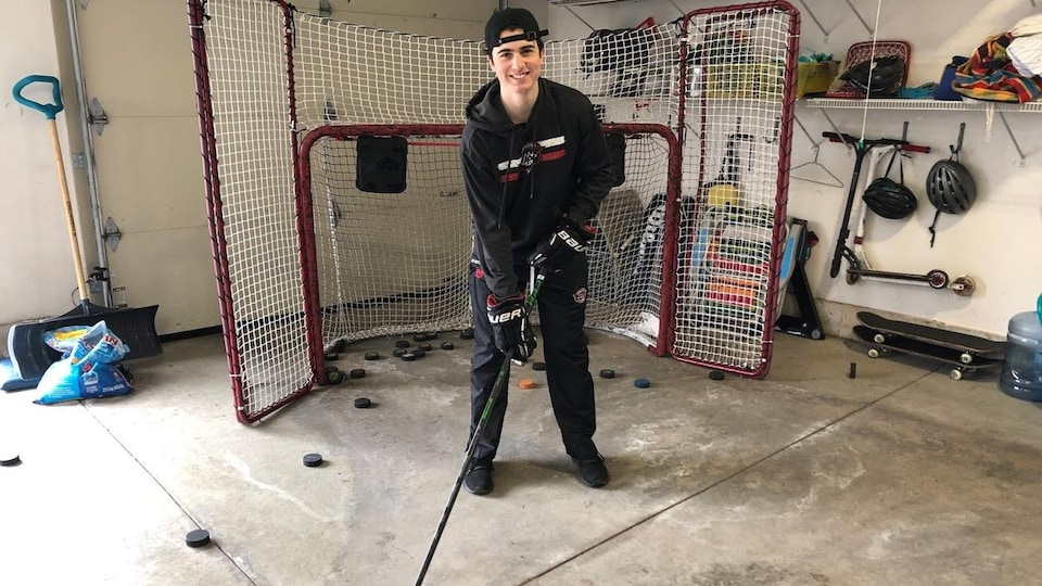 Homme jeune souriant, légèrement penché devant un but de hockey.