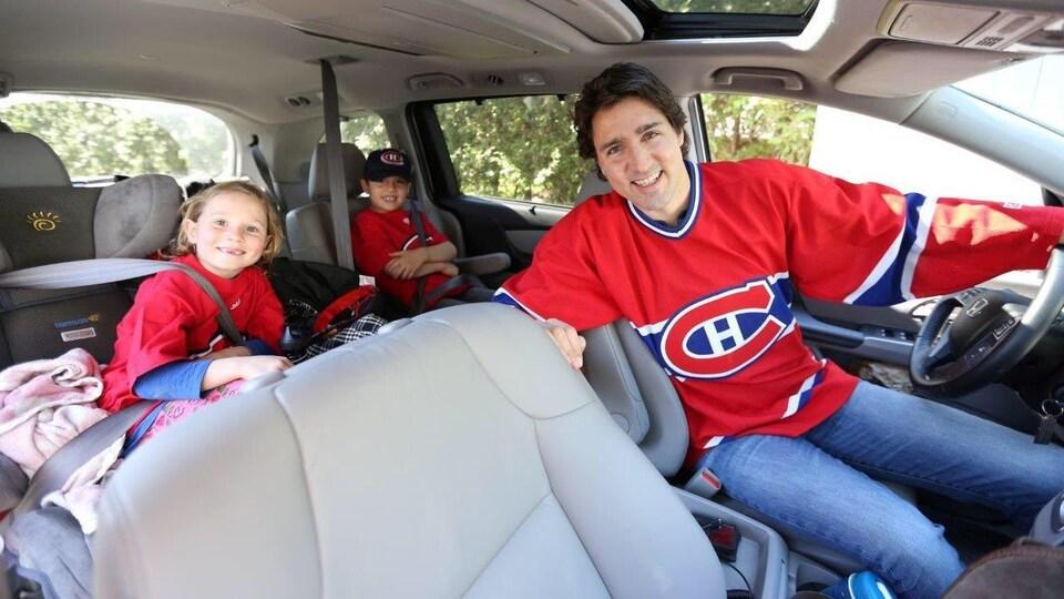 Justin Trudeau au volant d'une voiture avec un chandail du Canadien de Montréal sur le dos.