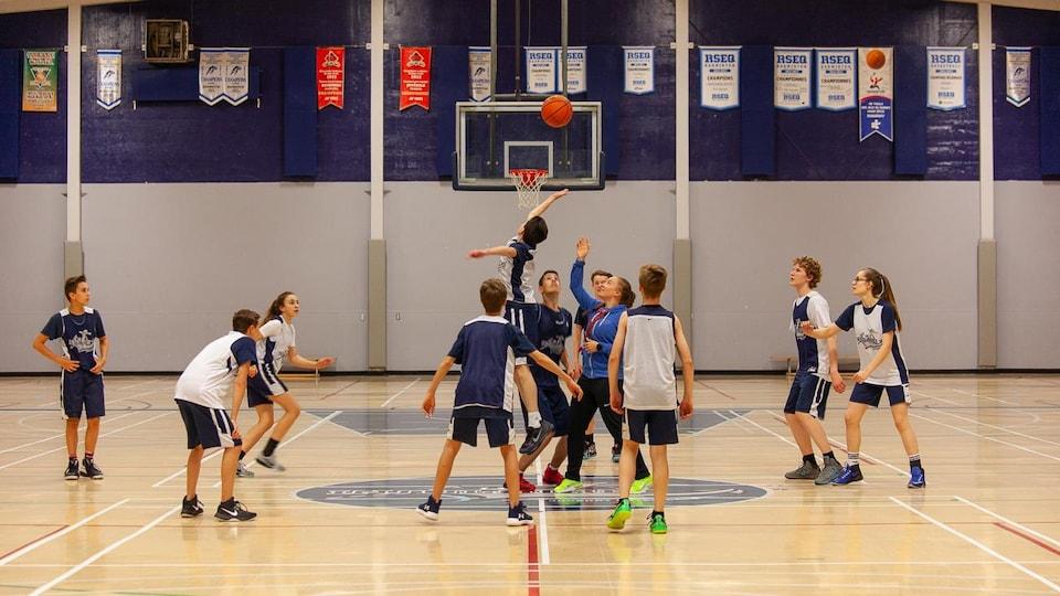 Une dizaine d'adolescents jouent au basketball.