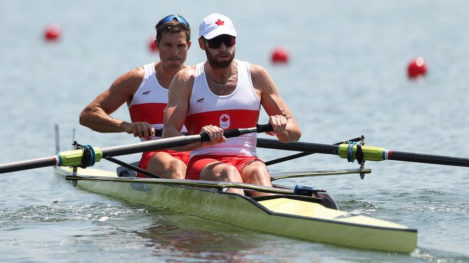 Deux rameurs canadiens en plein effort dans leur embarcation.