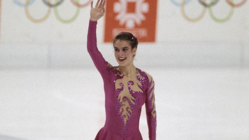 Elle est au centre de la glace et lève le bras droit dans les airs.