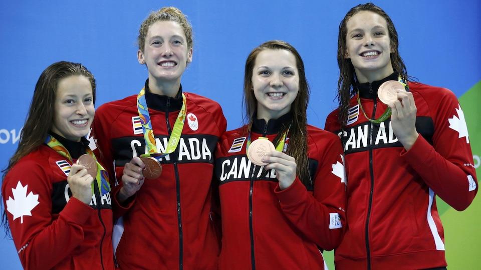 Elle sourit à la caméra avec sa médaille autour du cou avec trois de ses équipières.