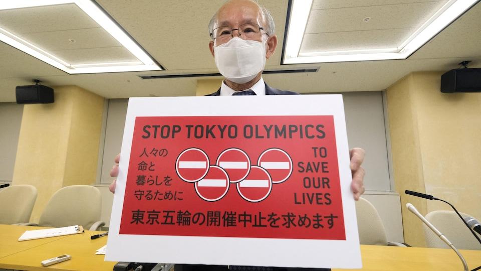 L'homme tient un carton avec le slogan Annulons les Jeux olympiques de Tokyo.