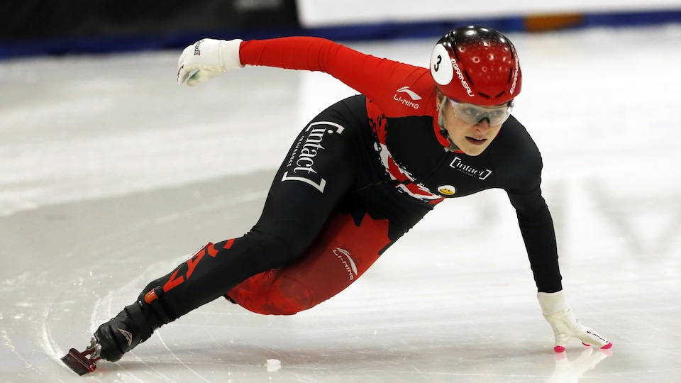 La patineuse, vêtue d'une combinaison rouge et noire, pose la main sur la glace lors d'un virage.