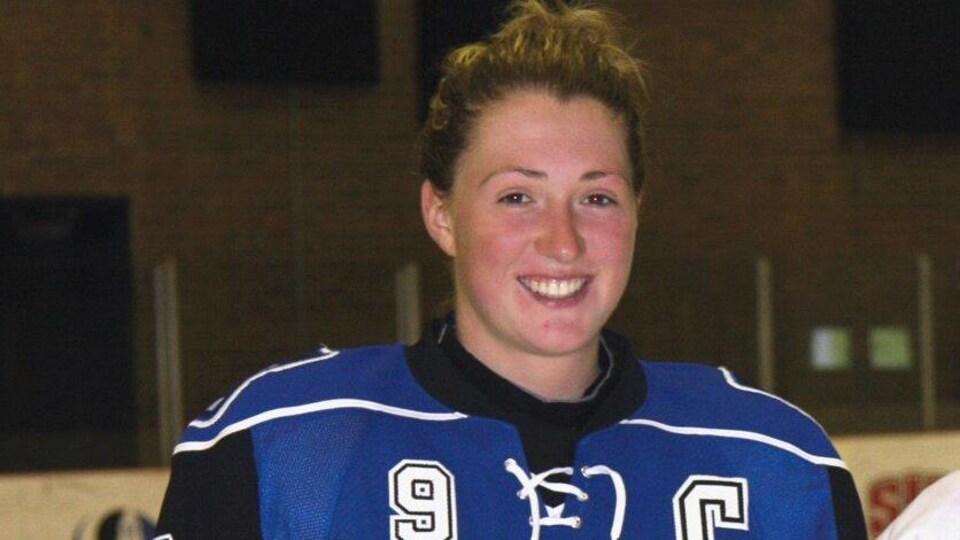 Kim Deschênes debout sur ses patins, habillée en hockey.
