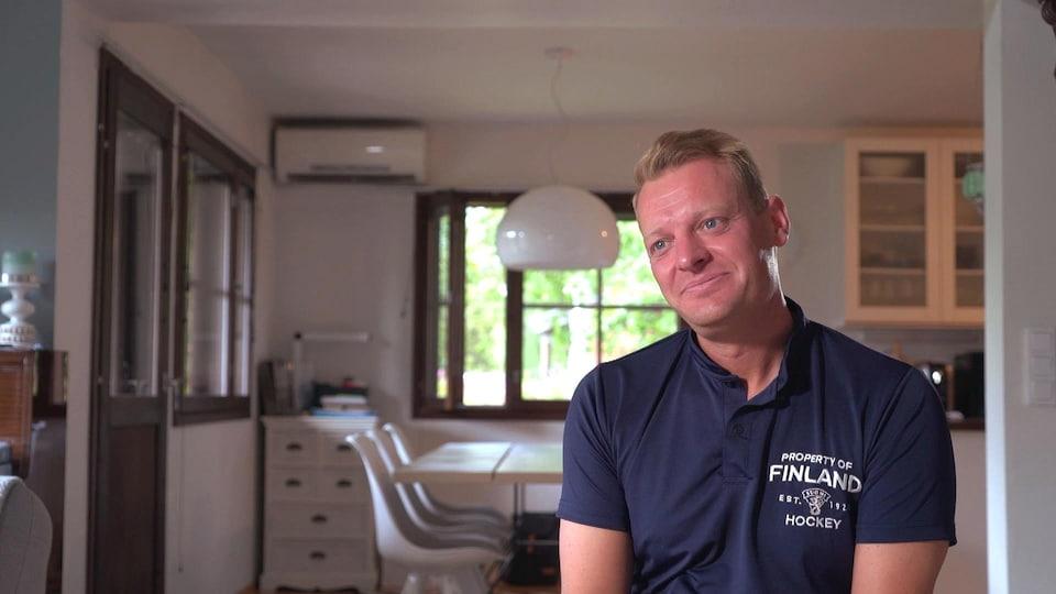 Un homme en entrevue sourit dans une cuisine
