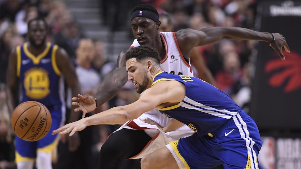 Ils luttent pour la possession du ballon pendant le 1er match de la finale entre les Warriors et les Raptors à Toronto.