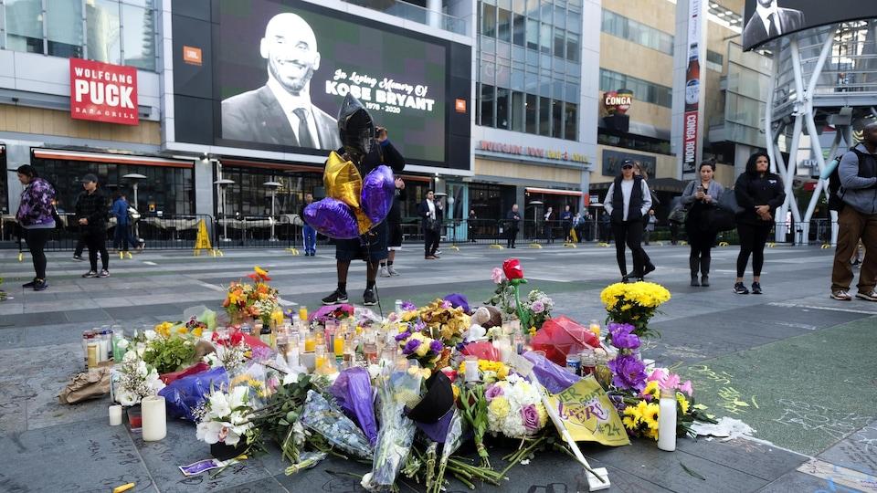 Un écran géant montre une photo à la mémoire de Bryant et des fleurs sont déposées par terre.