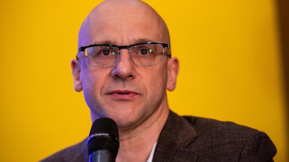 Plan rapproché d'un homme en conférence de presse, devant un fond jaune