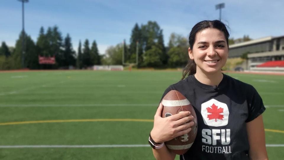 Elle offre un beau sourire en tenant un ballon de football sur un terrain.