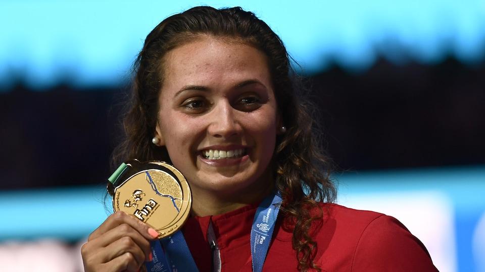 Elle montre sa médaille d'or.