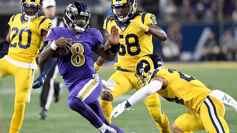 Lamar Jackson court avec le ballon.