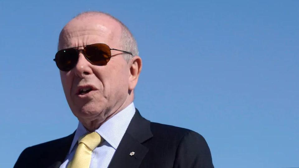 Un homme en complet porte des lunettes fumées. Il prononce un discours sous le soleil.