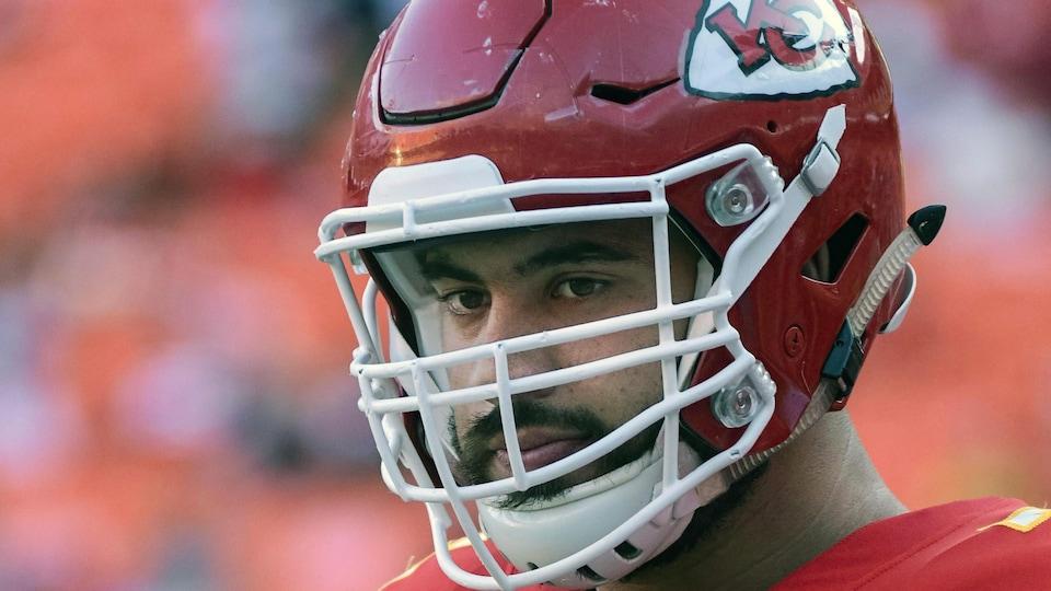 Gros plan d'un joueur qui porte un casque de football rouge.