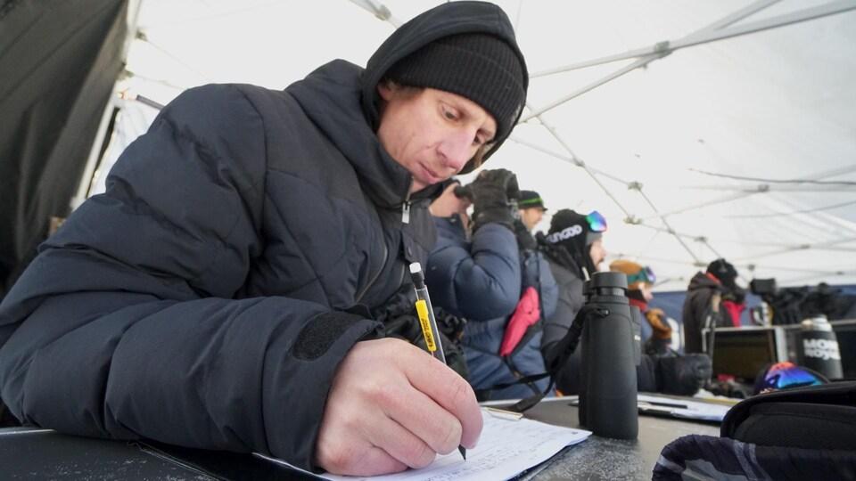 Il prend des notes sur une feuille avec un crayon à mine.
