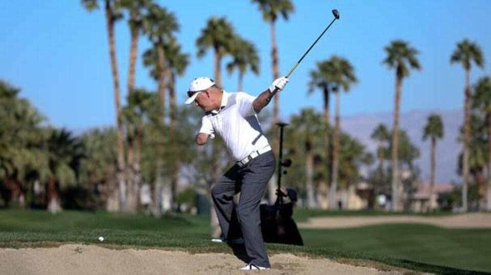 Le golfeur s'élance d'un seul bras,