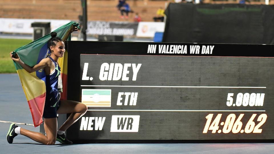 La coureuse pose près du tableau indicateur sur lequel son chrono record est affiché