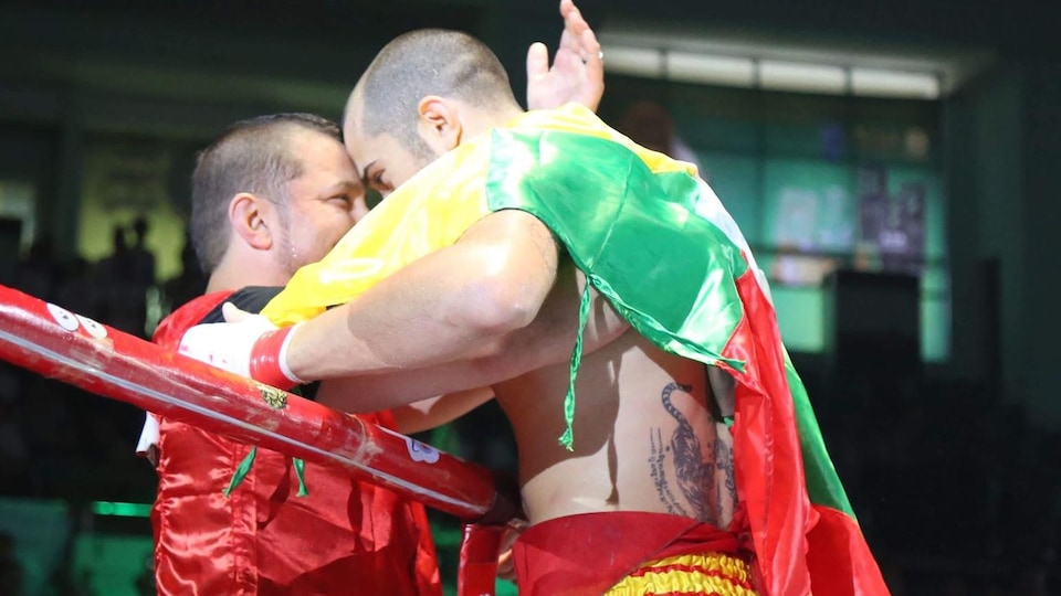 Le combattant Dave Leduc fait l'accolade à son mentor, Patrick Marcil, après sa victoire contre Diesellek Sanong