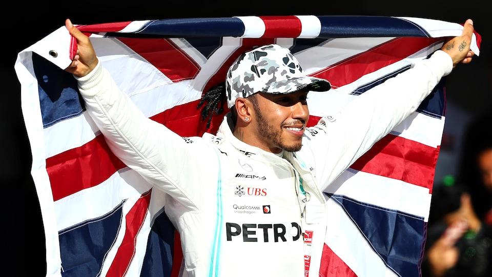 Il sourit et lève le drapeau britannique derrière son dos.