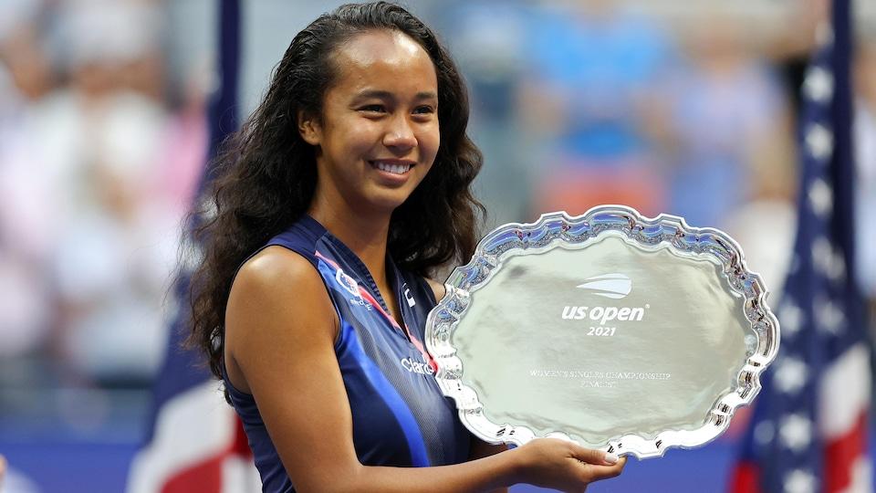 Elle tient la plaque de finaliste à New York.