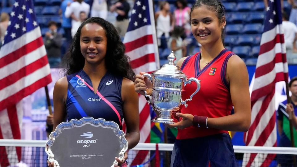 Les deux jeunes femmes sourient pour les caméras après le match, en tenant la plaque commémorative et le trophée.