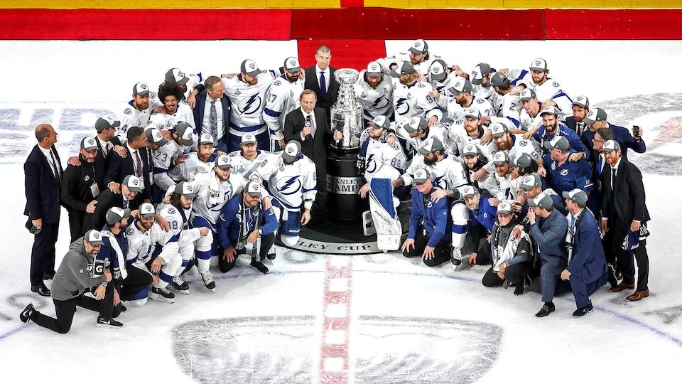 Des joueurs de hockey entourent la coupe Stanley.