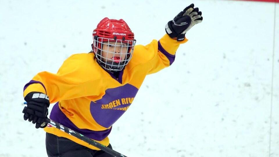 Une jeune joueuse de hockey célèbre après avoir marqué un but.