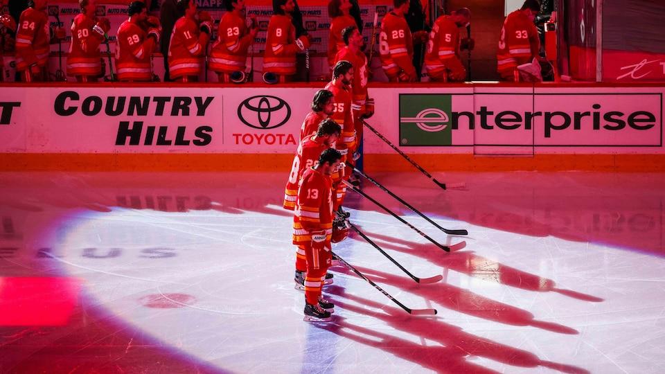 Des joueurs des Flames se tiennent debout devant leur banc pendant l'hymne national.
