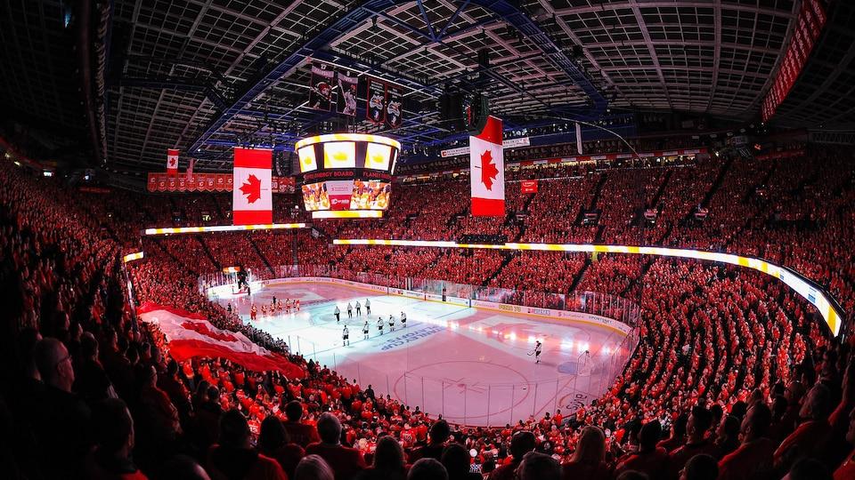 Photo du domicile des Flames de Calgary bondé de spectateurs, avec un drapeau canadien à l'écran géant.