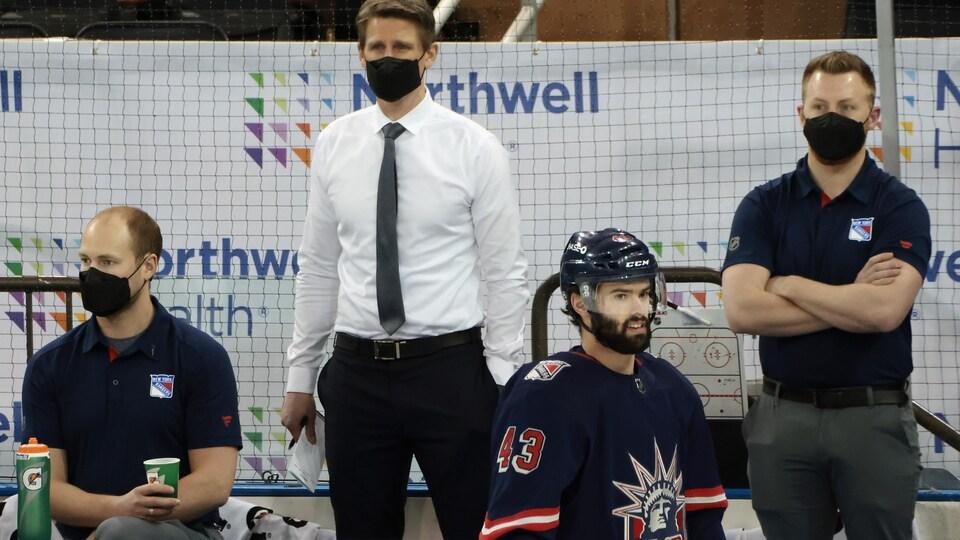 Des entraîneurs des Rangers observent un match, le visage couvert par un masque.