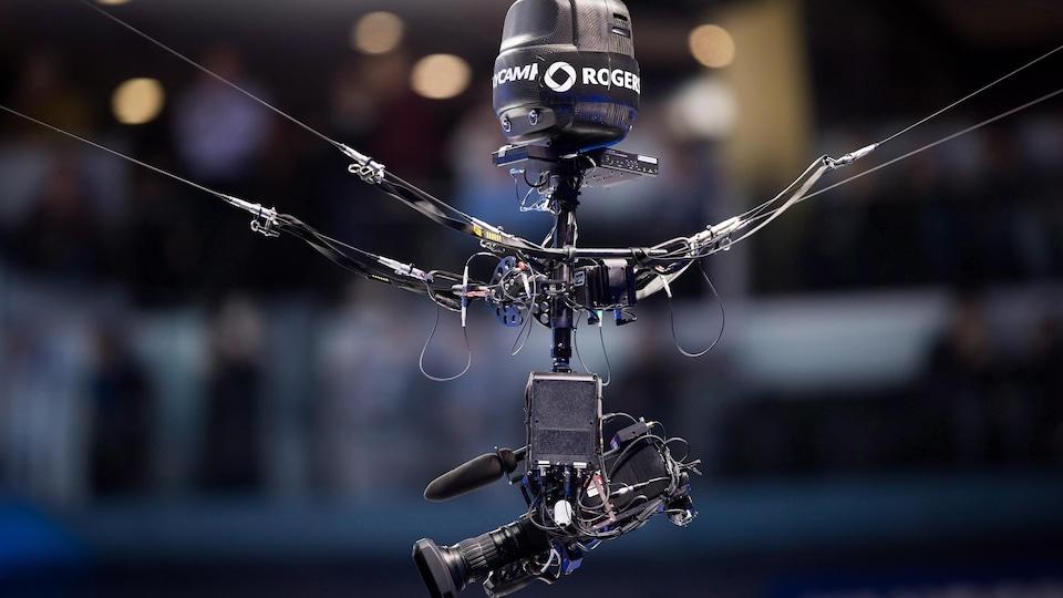 Une caméra survole une surface de jeu, accrochée par de longs câbles.