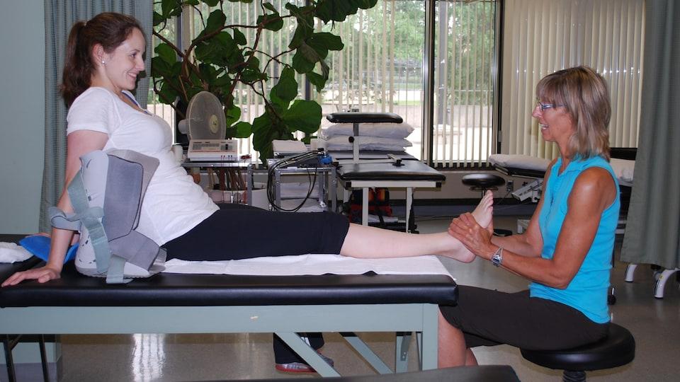 Elle manipule le pied gauche d'une patiente.