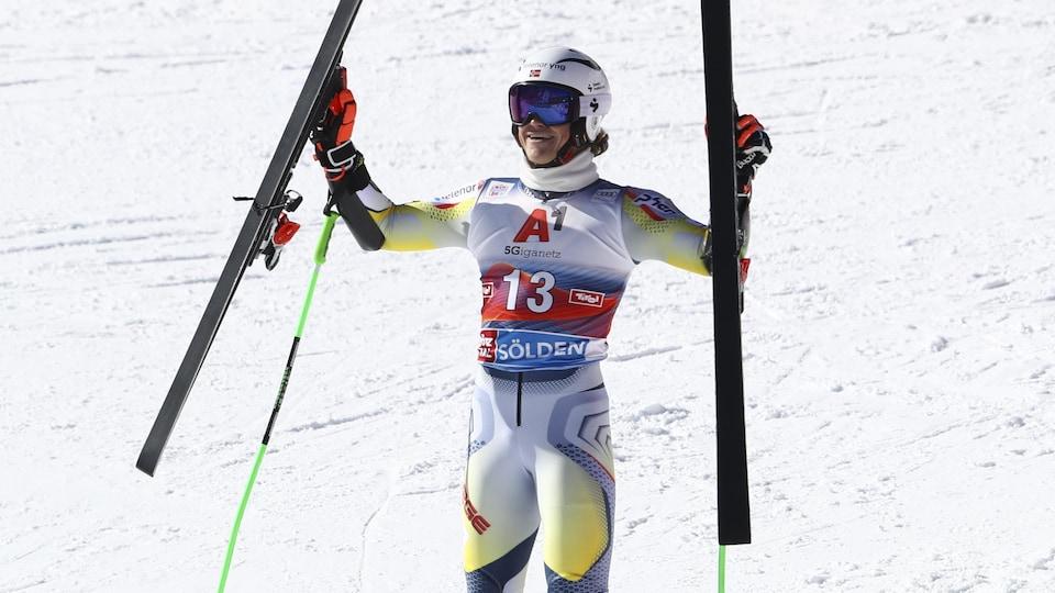 Il célèbre sa victoire en levant ses skis.