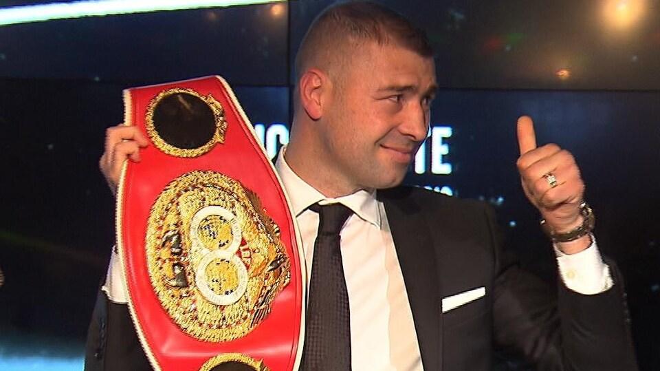 Il tient sa ceinture de champion de la main droite et lève le pouce gauche.