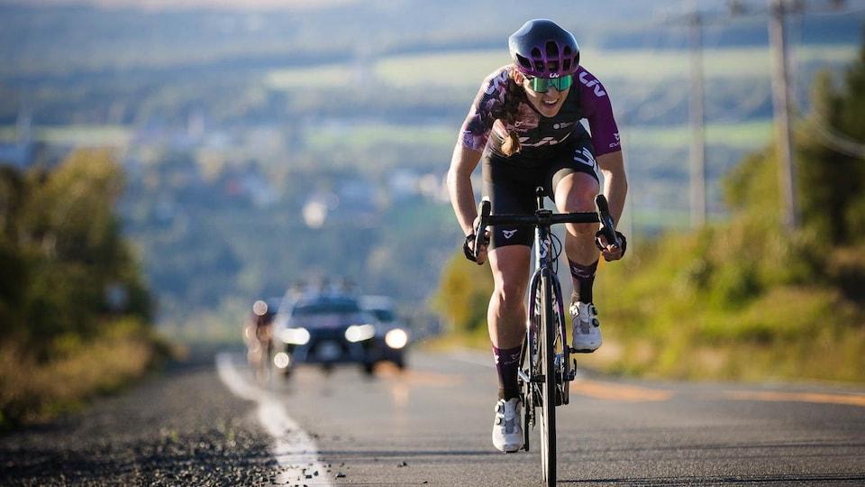 La cycliste grimace d'effort en faisant l'ascension d'une pente.