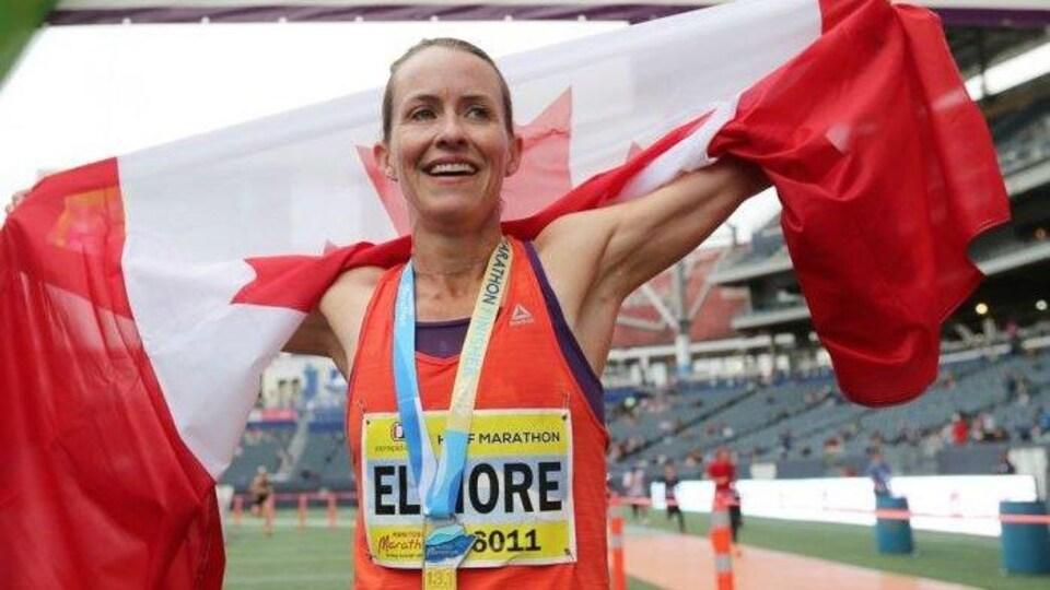 Sourire aux lèvres, elle porte le drapeau canadien sur ses épaules.
