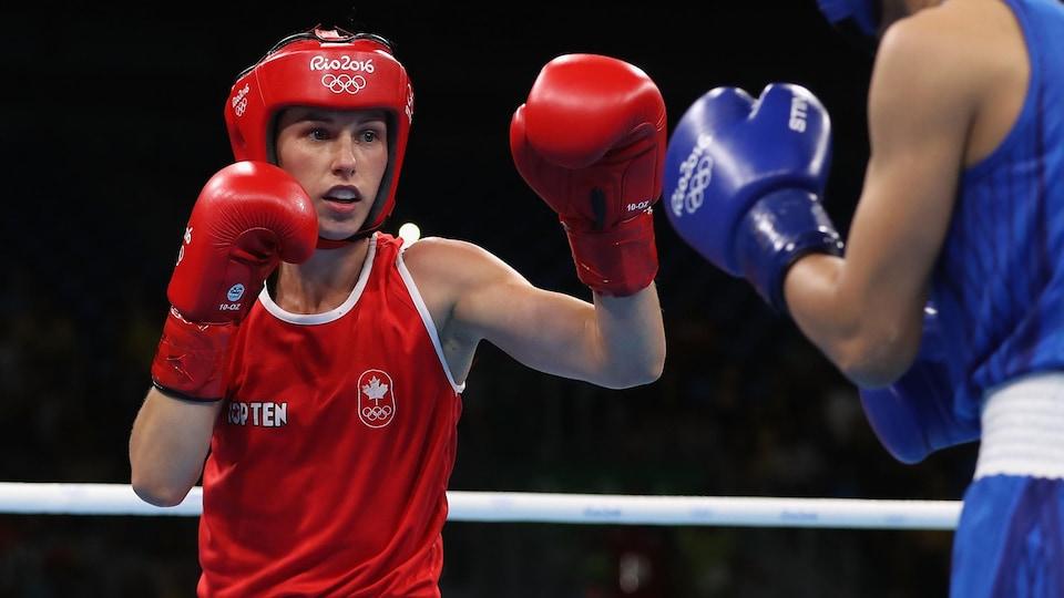 La boxeuse, vêtue de rouge, est en plein combat.