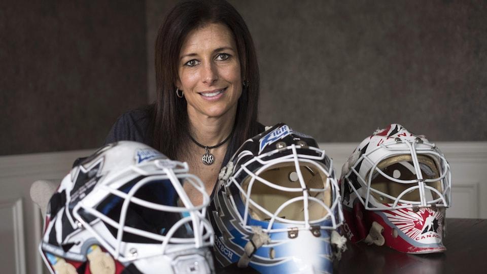 Elle pose devant trois casques de gardienne de but de hockey.