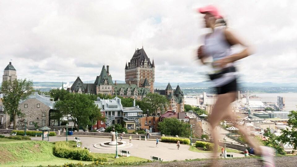 Une coureuse passe devant l'objectif de la caméra pointé sur le Château Frontenac.