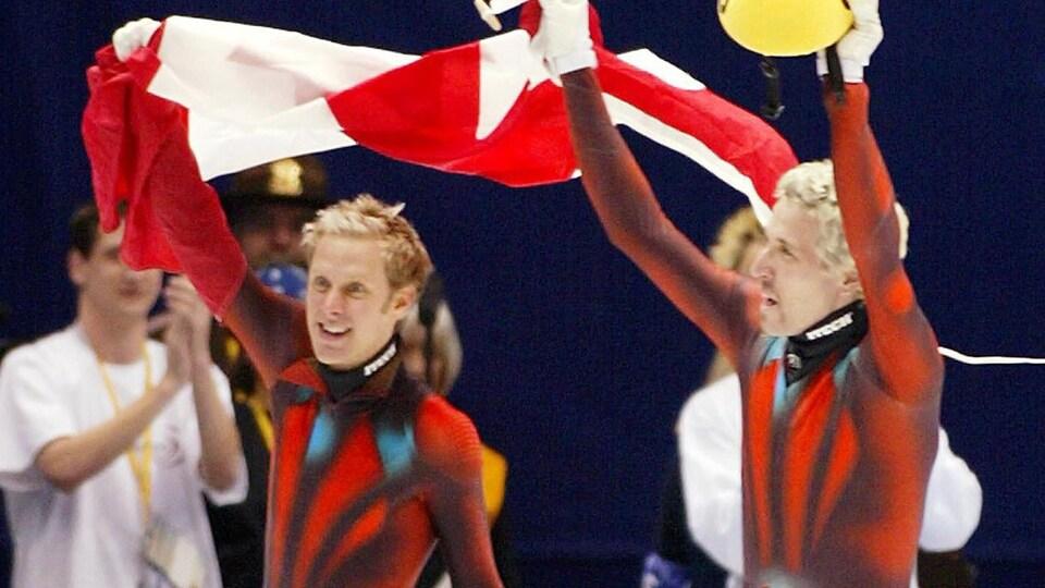 Les deux patineurs brandissent le drapeau canadien.