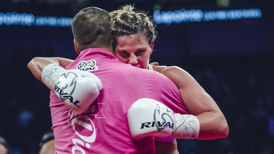 Une boxeuse et son entraîneur se serrent dans leurs bras sur le ring.