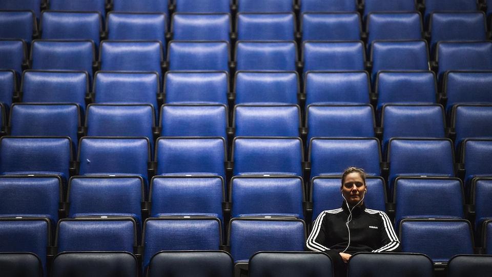 Marie-Eve Dicaire assise dans les gradins vides du Centre Vidéotron.