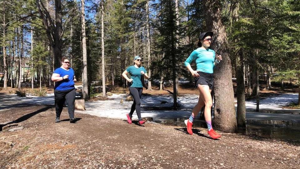 Trois femmes courent dans un sentier en forêt.