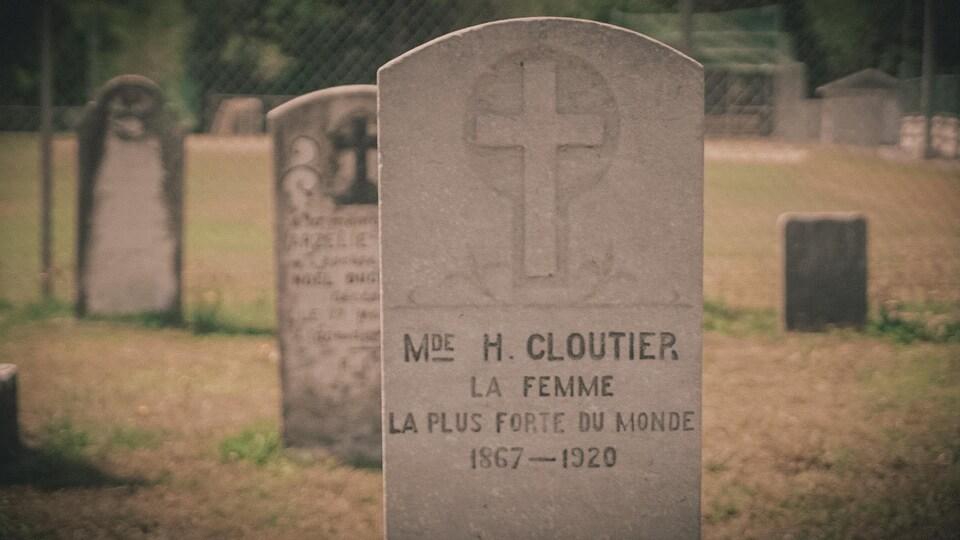 Une pierre tombale sur laquelle on peut lire : « Madame H. Cloutier, la femme la plus forte au monde ».