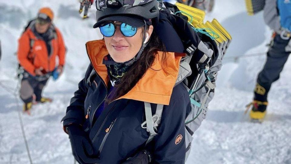 Une femme grimpe l'Everest en compagnie de cinq hommes à l'arrière.