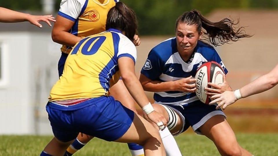 Une joueuse de rugby accroupie tente un changement de direction