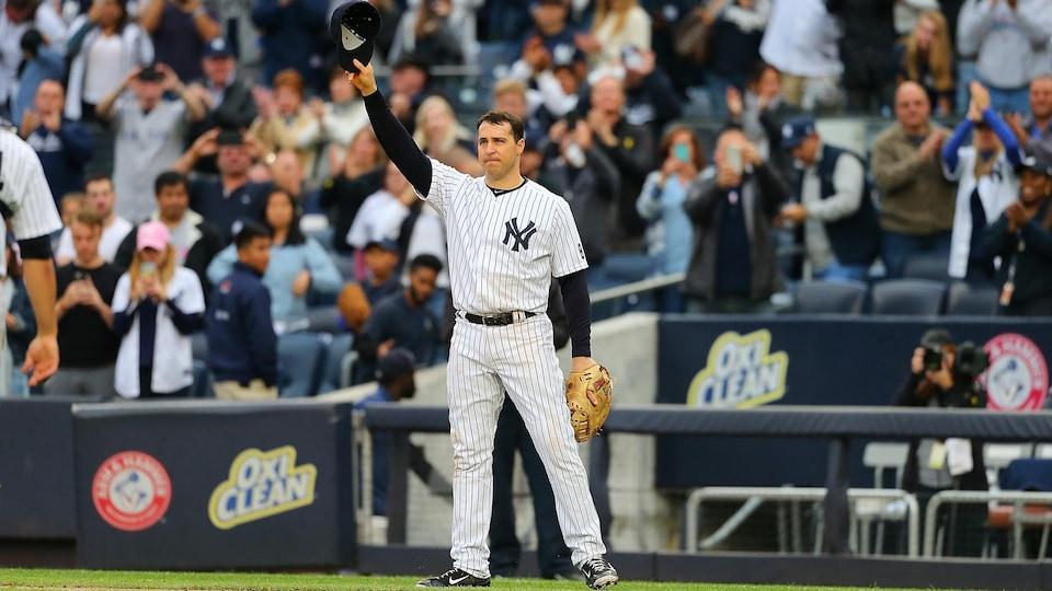 Il salue les supporteurs des Yankees de New York.