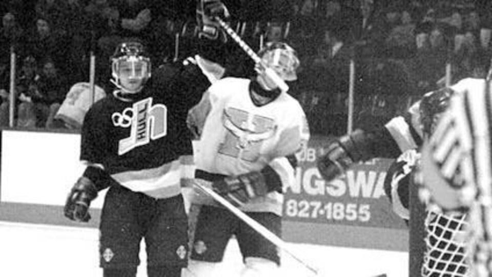 Un joueur de hockey lève son bras dans les airs après avoir marqué un but.
