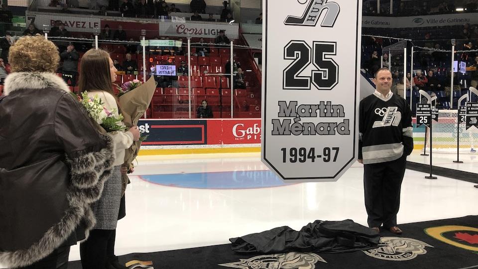 Un ancien joueur de hockey se tient devant une affiche avec son numéro