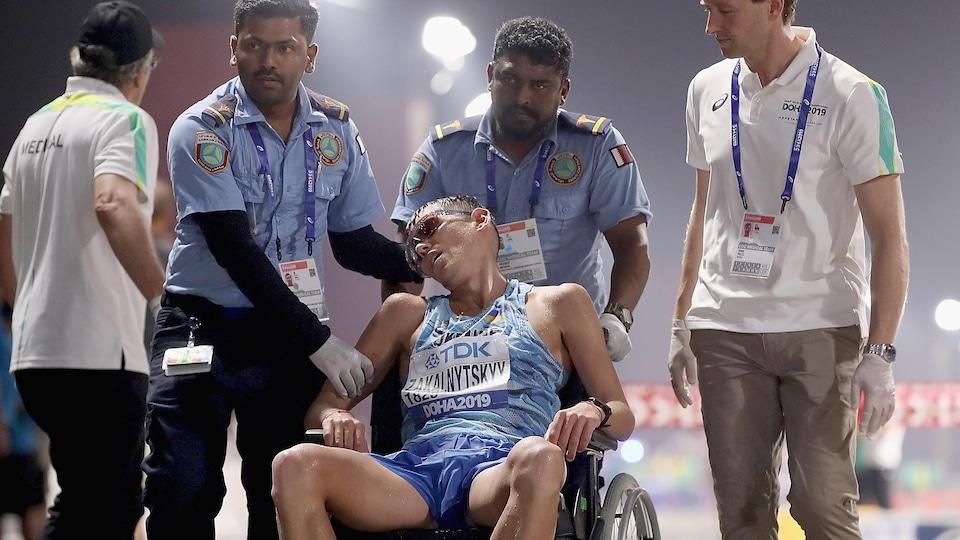 Il est escorté hors du stade de Doha en fauteuil roulant après le 50 km marche.